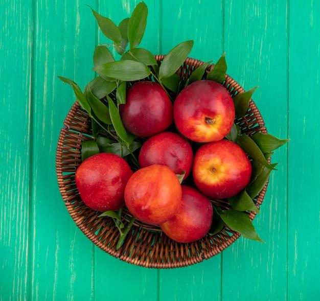 緑の表面にバスケットに葉の枝と桃のトップビュー