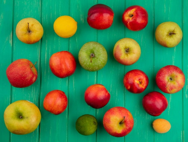 緑の表面にリンゴと桃とライムとレモンのトップビュー