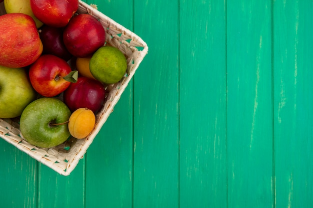 緑の表面にリンゴとバスケットにライムと桃のトップビュー