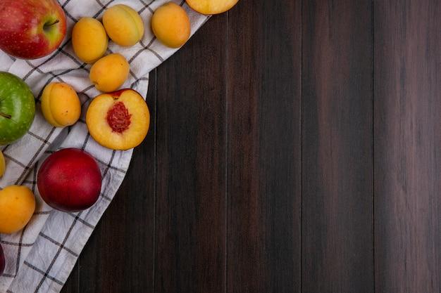 Вид сверху персиков с абрикосами и яблоками на полотенце на деревянной поверхности