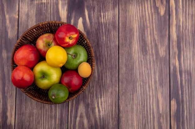 木の表面にバスケットに着色されたリンゴと桃のトップビュー