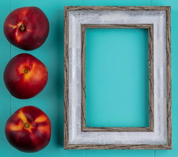 Вид сверху персиков с серой рамкой на синей поверхности