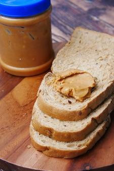 Вид сверху арахисового масла и стопки хлеба на столе