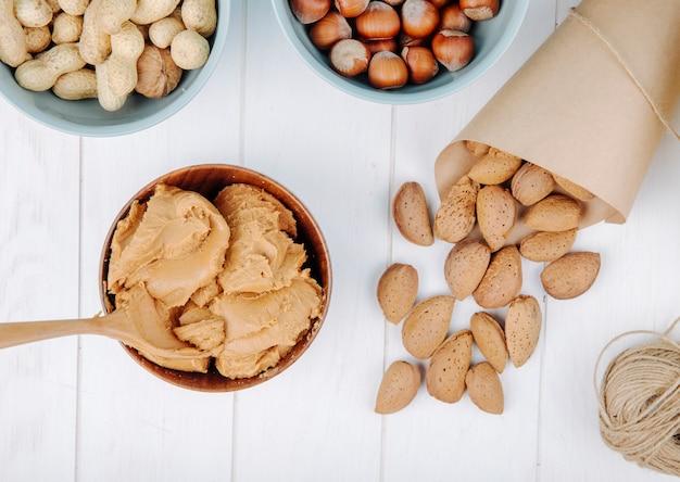 Вид сверху арахисового масла в миску и миндаль в скорлупе, разбросанных на белом фоне