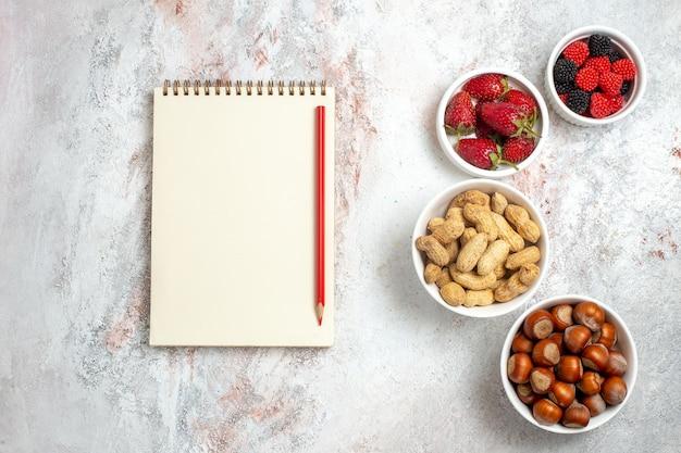 白い表面に新鮮なイチゴとピーナッツとヘーゼルナッツの上面図