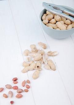Вид сверху арахиса в миску с ореховым крекером и раковиной