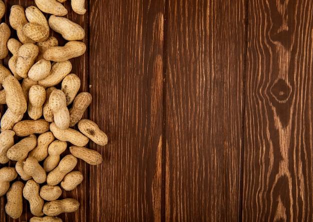 Вид сверху арахиса в скорлупе, разбросанных на деревянном фоне с копией пространства