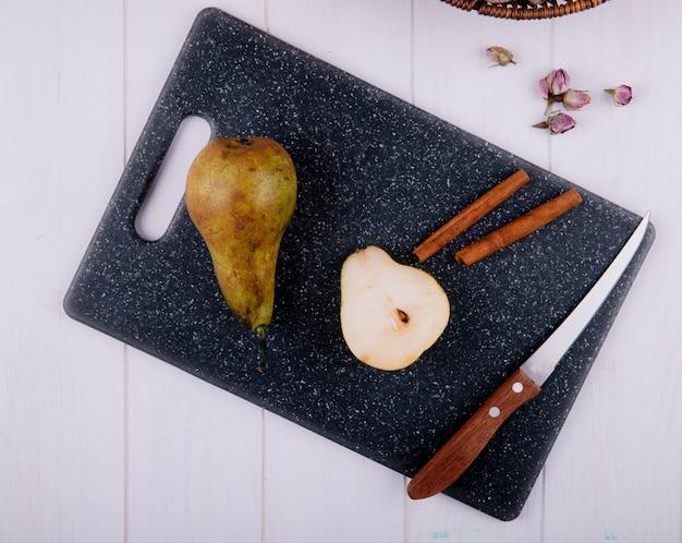 白い木製の背景に黒のまな板にシナモンスティックと包丁と梨のスライスのトップビュー