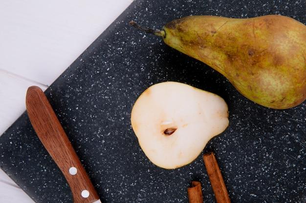 白い木製の背景に黒のまな板にシナモンスティックと包丁と梨のスライスのトップビュー 無料写真