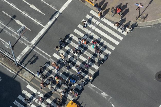 Вид сверху на пешеходов толпы неопределенных людей, идущих на эстакаде перекресток перекресток