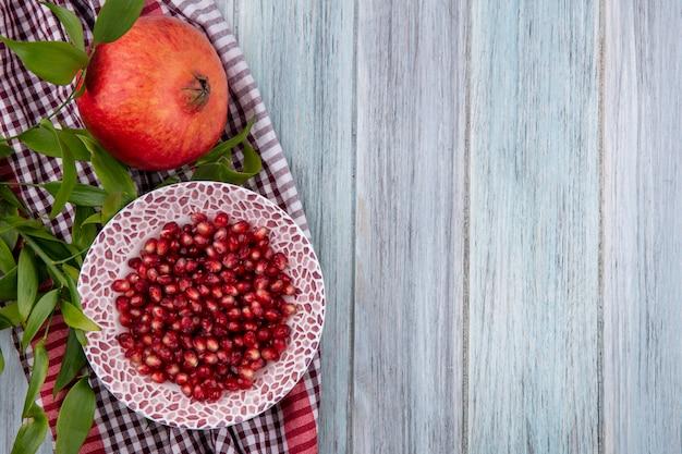 Вид сверху очищенного граната на тарелке на красном клетчатом полотенце на серой поверхности