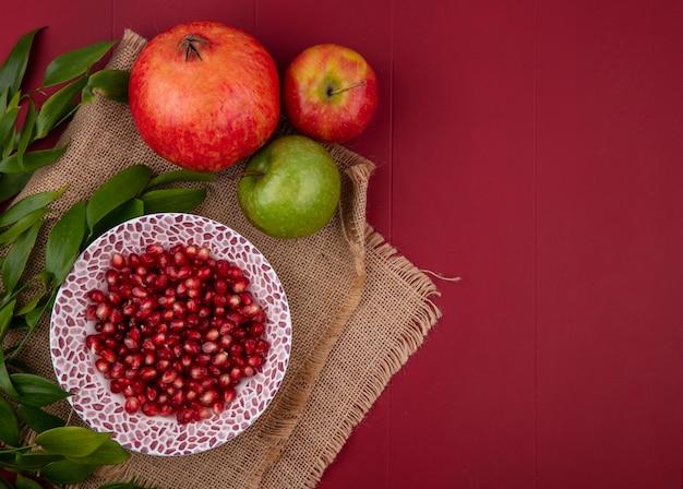 Вид сверху очищенного граната на тарелке с яблоками и ветвями листьев на красной поверхности