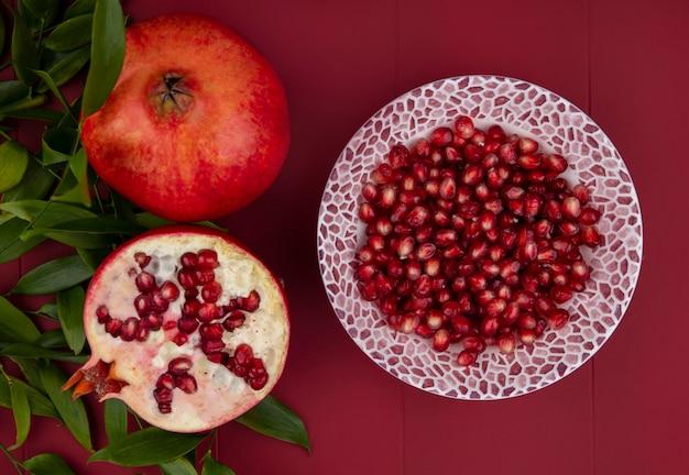 Вид сверху очищенного граната на тарелке с ветвями листьев на красной поверхности