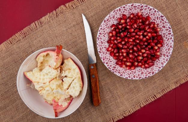 Вид сверху очищенного граната на тарелке с кожурой и ножом на бежевой салфетке