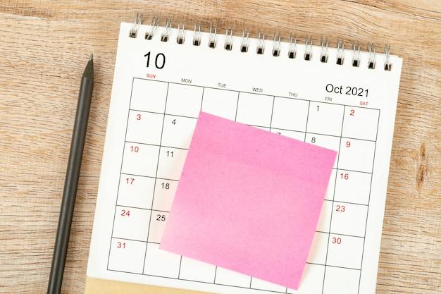 ペンの上面図、カレンダーの計画と期限、木製の背景に付箋、10月のカレンダーデスク2021