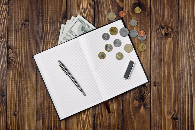 펜, 오픈 노트, 플래시 드라이브, 지폐 및 동전의 상위 뷰