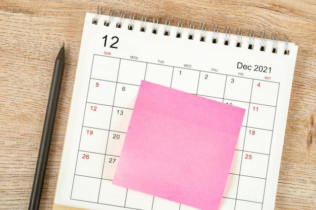 鉛筆の上面図、カレンダーの計画と期限、木製の背景に付箋、12月のカレンダーデスク2021