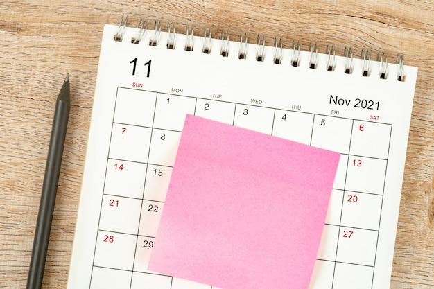鉛筆の上面図、カレンダーの計画と期限、木製の背景に付箋、11月のカレンダーデスク2021