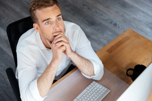 Вид сверху задумчивого молодого бизнесмена, работающего с компьютером и мышления на рабочем месте