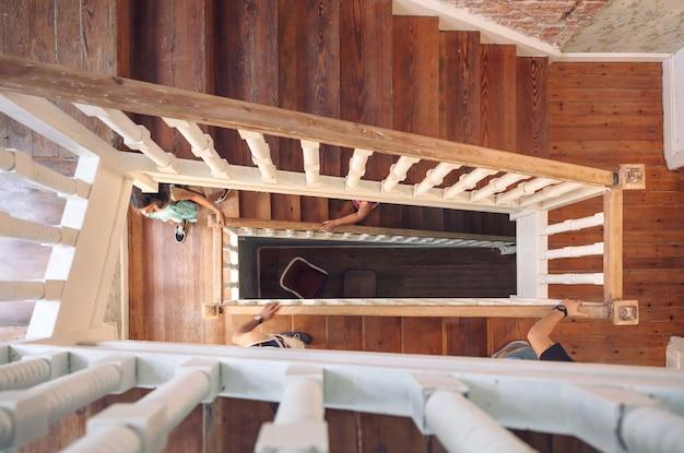 나무 난간을 들고 집 계단을 등반하는 사람들의 손의 상위 뷰