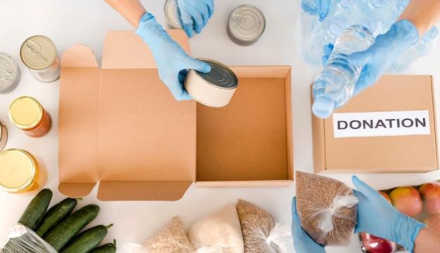 Вид сверху людей, готовящих коробку с пожертвованием пищи