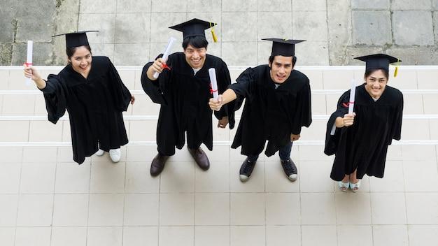 卒業式のガウンと帽子を立て、卒業証書を持っている人々のトップビュー。