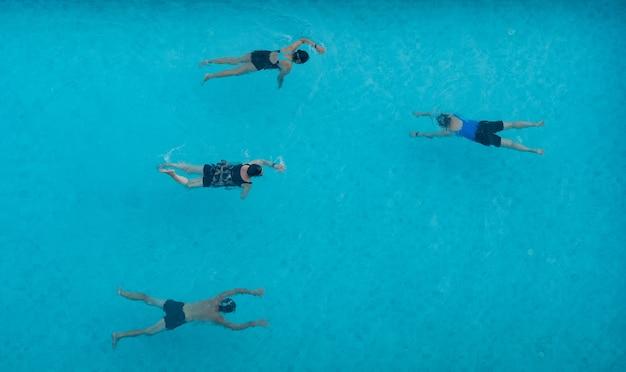 プールで泳いでいる人々のトップビュー