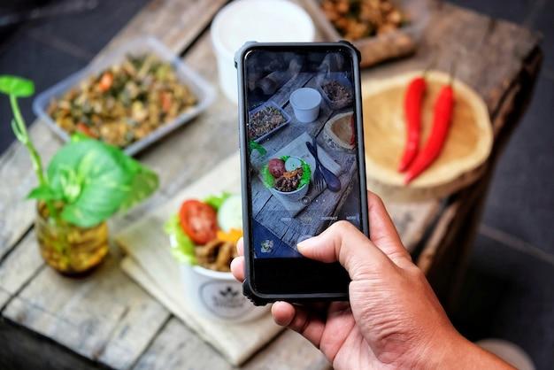 電話を使用して食べ物の写真を撮っている人々の上面図、人々は自宅で食べ物の写真を撮る