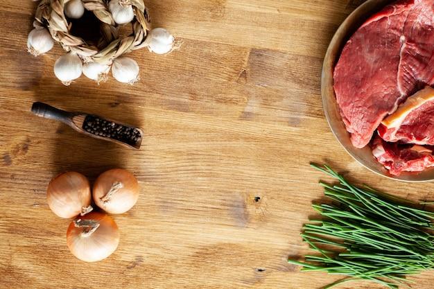 두 개의 붉은 고기 덩어리 옆에 있는 후추 콩의 상위 뷰. 복사 공간이 있습니다.