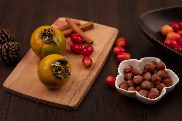 木製の表面に分離されたコーネリアンチェリーとボウルにヘーゼルナッツとシナモンスティックと木製のキッチンボード上の柿の果実の上面図