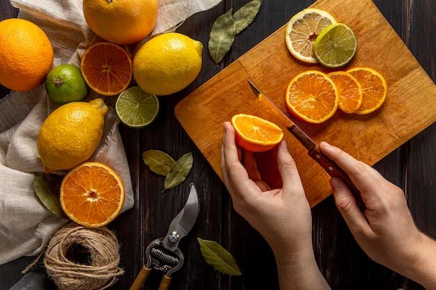 柑橘系の果物を刻んでいる人のトップビュー