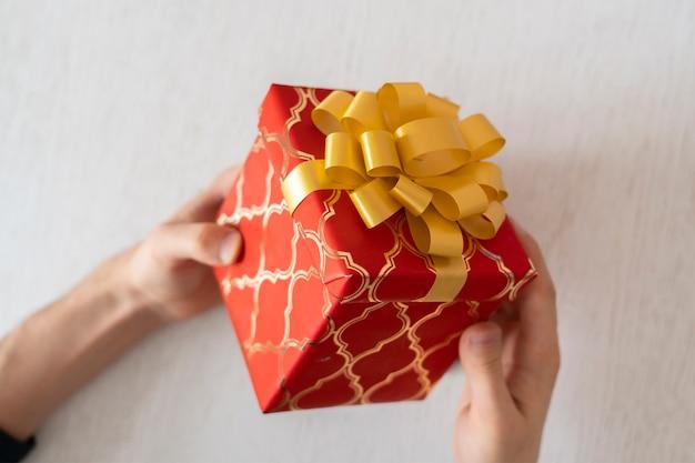 Вид сверху рук человека с подарочной коробкой