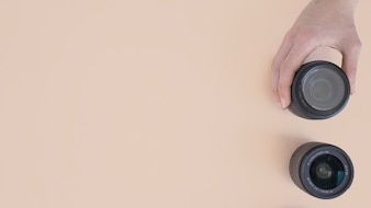 Top view of person's hand holding modern camera lens on beige background