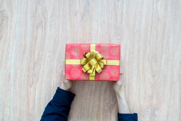 Вид сверху на руки человека, держащего подарочную коробку с праздничным подарком