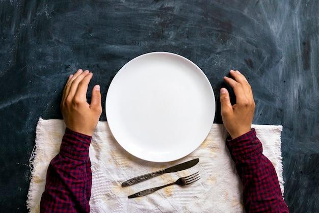 空のプレートとテーブルの上の人の手の上面図