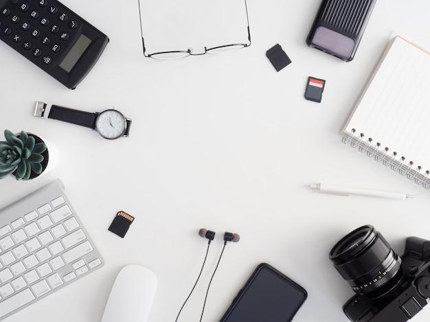 Вид сверху рабочей станции фотографа, концепции рабочего пространства с цифровой камерой, картой памяти, клавиатурой и смартфоном на белом фоне стола
