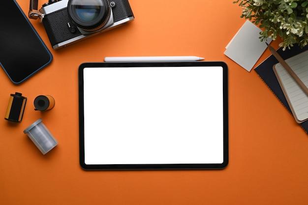 주황색 배경에 디지털 태블릿, 카메라, 커피 컵, 노트북이 있는 사진가 작업장의 최고 전망.