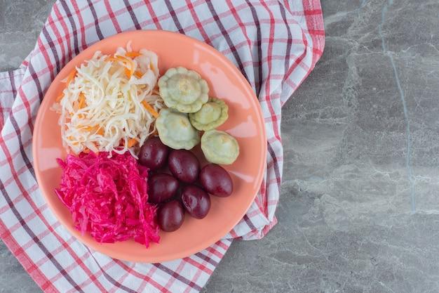 Вид сверху маринованных овощей на оранжевой тарелке