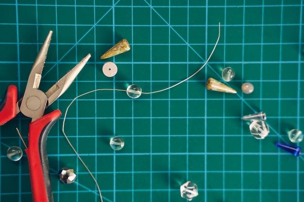 Вид сверху изображения различных деталей для ювелирных изделий ручной работы, изолированные на зеленом фоне