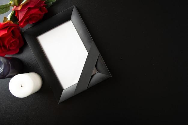 어두운 벽에 붉은 꽃과 촛불 액자의 상위 뷰