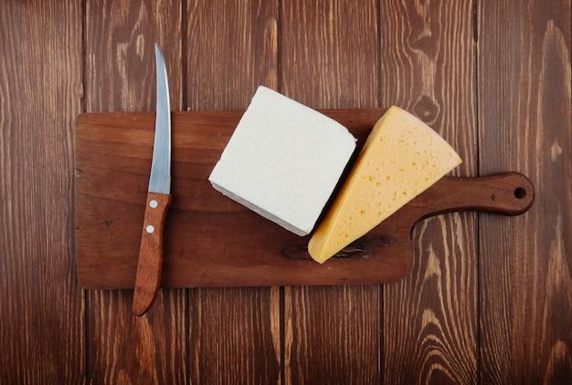 素朴な木製のテーブルに木製のまな板に包丁とチーズの部分のトップビュー