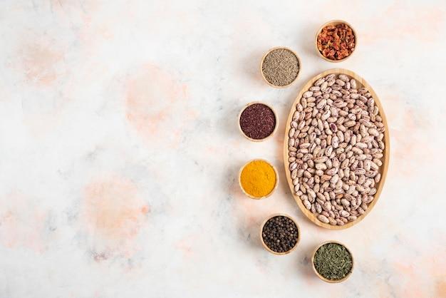 白いテーブルの上にさまざまな種類のスパイスと豆の山の上面図。