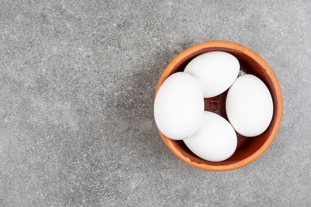 灰色のテーブルの上の陶器のボウルに卵の山の上面図。