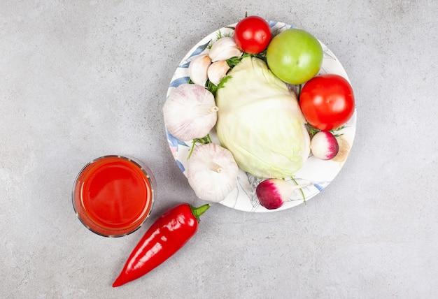 灰色の表面上のプレートとソースの上の有機野菜の山の上面図。