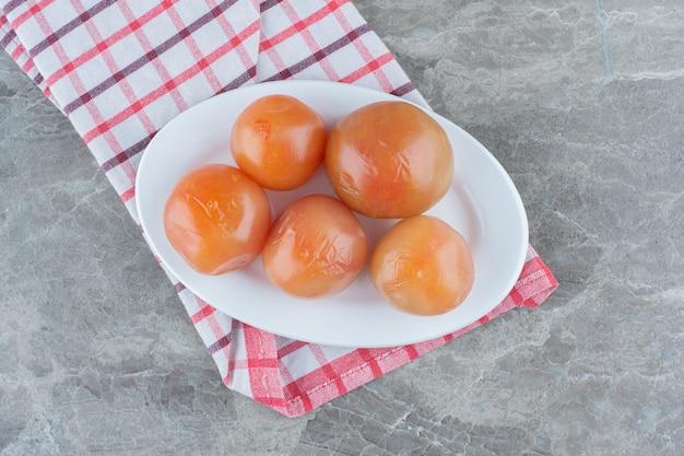 Вид сверху на кучу красных консервированных помидоров на белой тарелке.