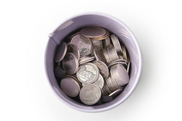 Вид сверху на кучу тайских монет в банке, изолированные на белом фоне, экономя деньги.