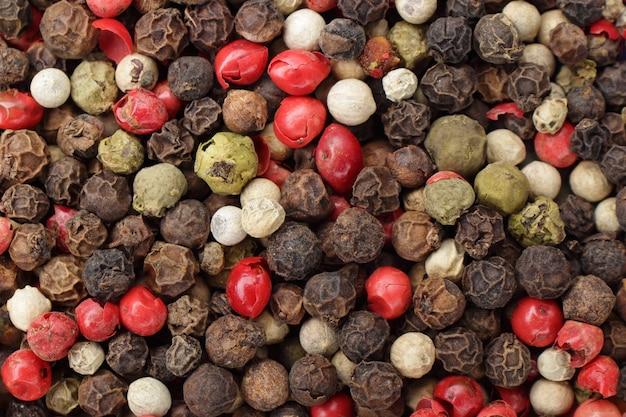 さまざまな胡椒の山の上面図、クローズアップ。黒、白、緑、赤の乾燥コショウの実を混ぜます。