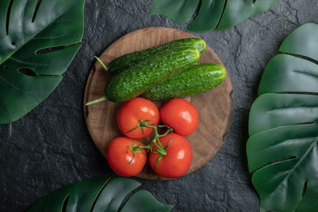 木の板に野菜の山の上面図。きゅうりとトマト。
