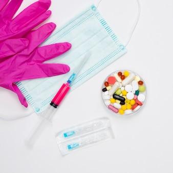 Вид сверху таблетки с хирургическими перчатками и медицинской маской