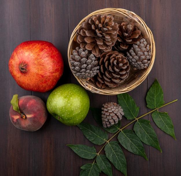 Вид сверху на сосновые шишки в ведре со свежими фруктами, такими как гранатовая груша и зеленое яблоко на деревянной поверхности